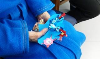Anziana tiene tra le maniil cuore e i cioccolatini regalati dagli studenti